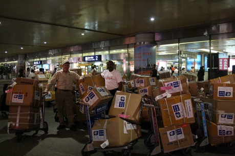 OBI staff collects boxes of disaster relief supplies at the Chengdu airport in China.