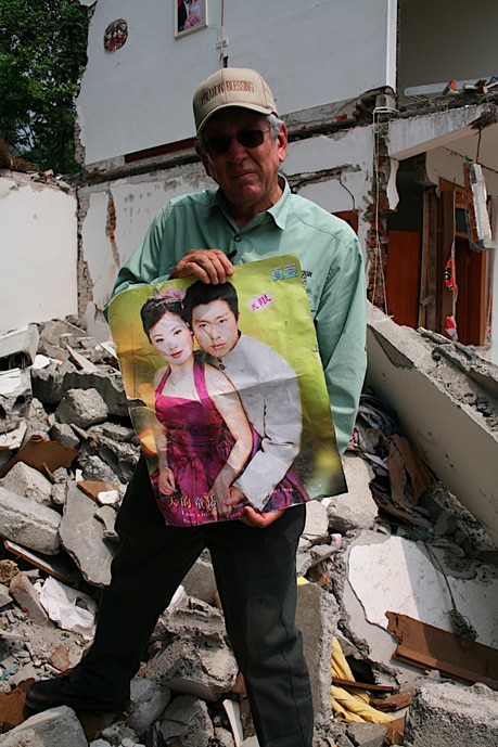 An Operation Blessing relief worker holds a photo found in the rubble of the couple that owned the house.