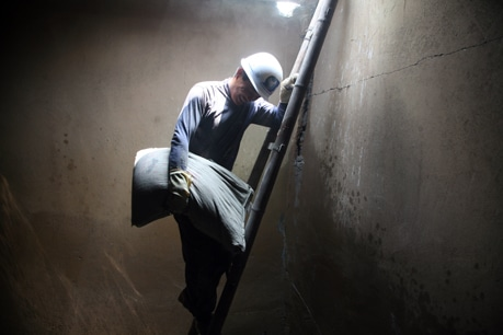 A worker descends into the large water storage tank to repair damaged concrete.