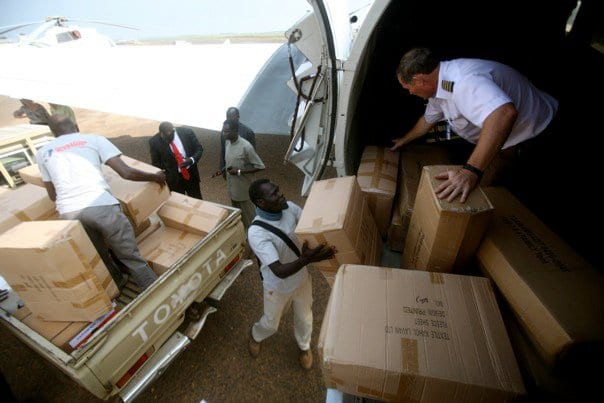 Teams unload boxes of food, medicine and other aid for South Sudan