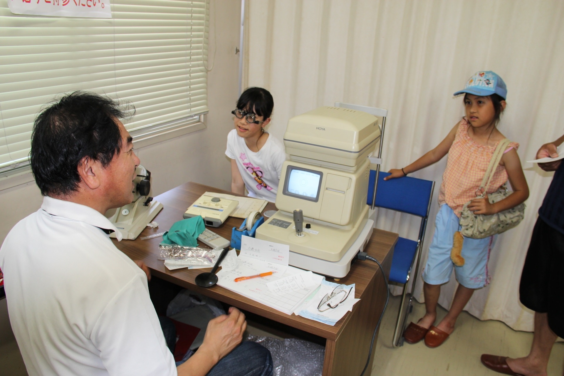 In Japan, girls receive eye exams as part of an ongoing disaster relief project after the devastating tsunami.