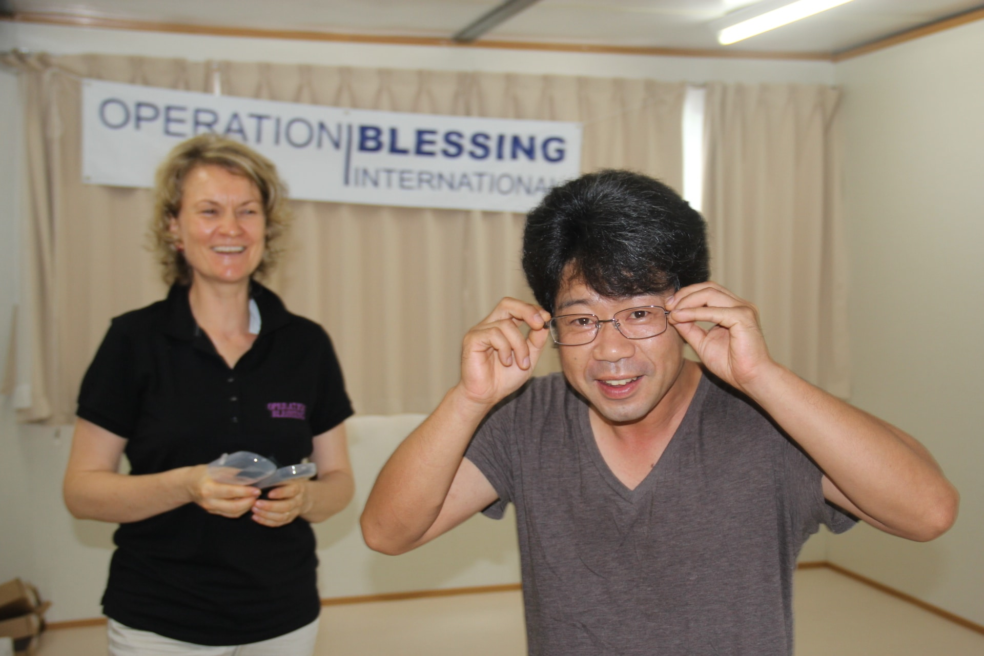 A man tries on his new eyeglasses from Operation Blessing in Japan.
