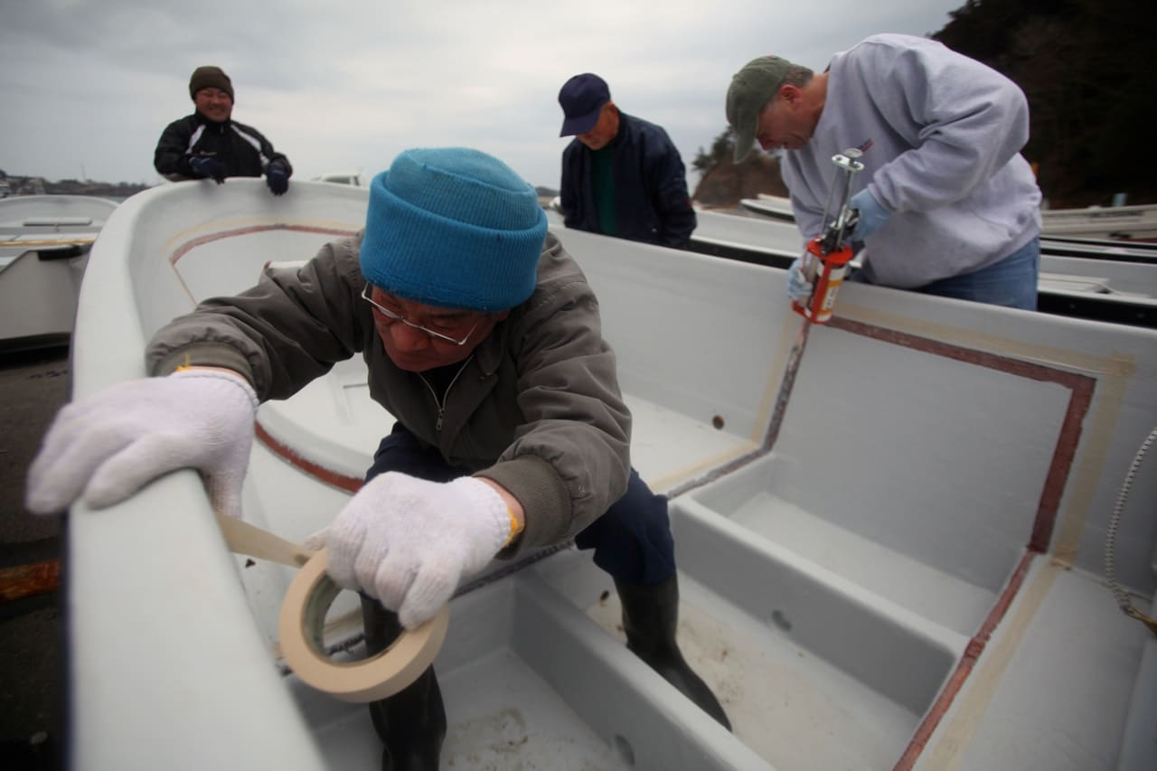 Fishermen and Maine boat builders work together to assemble final pieces of boats