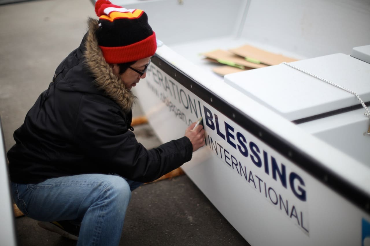 Teams apply Operation Blessing and SAP logos to the boats.