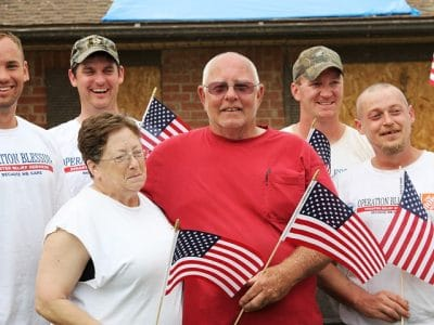 Steve, a retired combat veteran, and his wife stand with the team of Operation Blessing relief workers who helped work on their damaged home in Moore, Oklahoma.