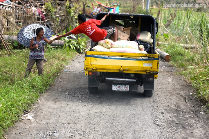 Operation Blessing teams delivering relief to victims by truck.