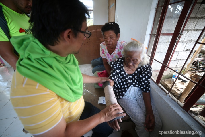 An elderly typhoon victims receives medical care from Operation Blessing teams.