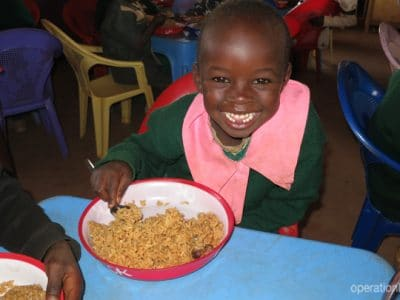 A Kenyan girl enjoys a meal as part of the celebration.