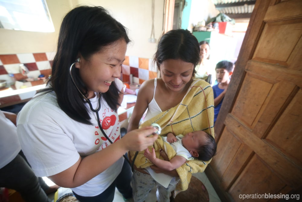 Operation Blessing Philippines medical clinic examines baby Yolanda after typhoon