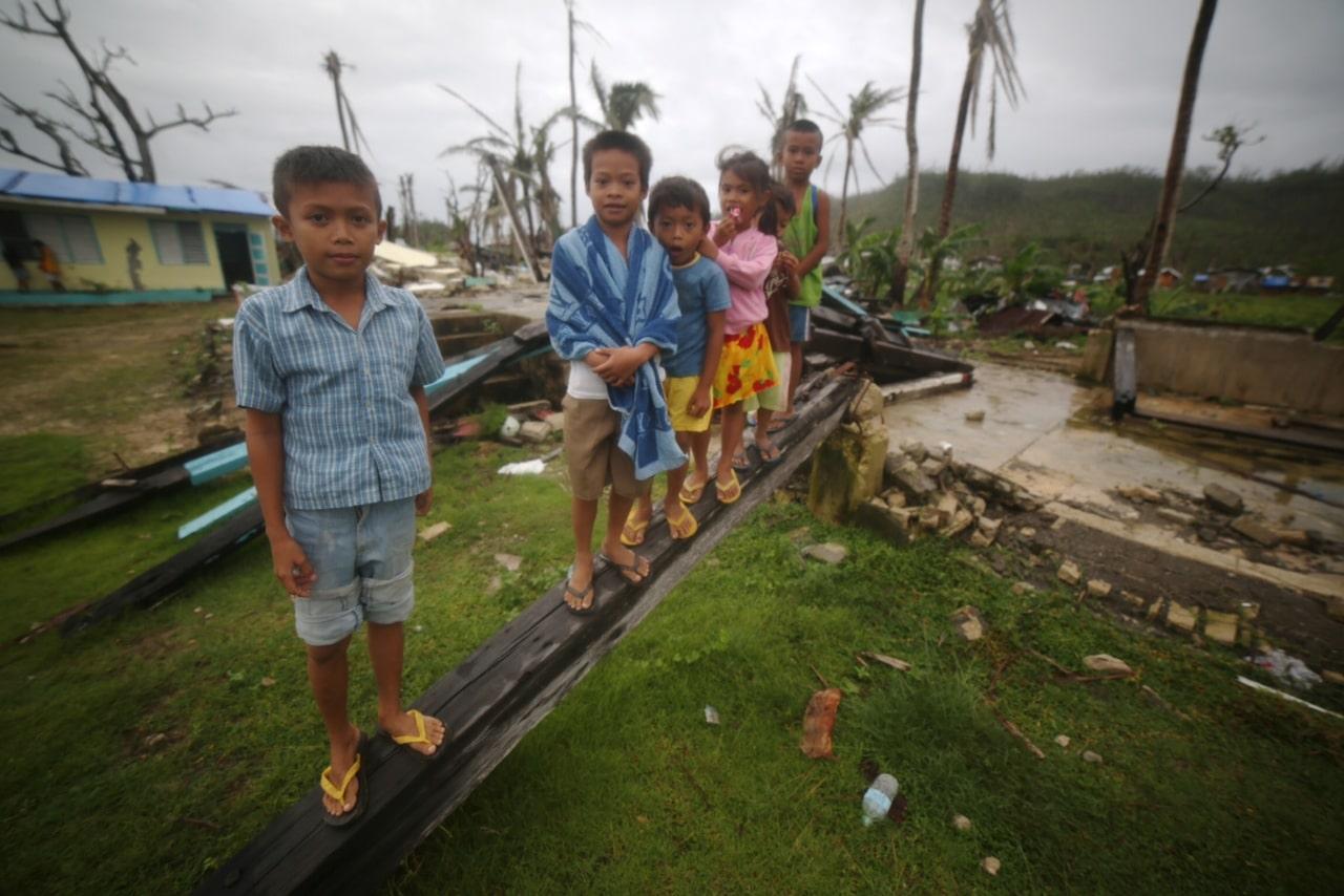 Children play near their destroyed school
