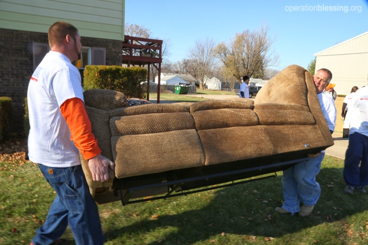 Teams carry a new couch into the home
