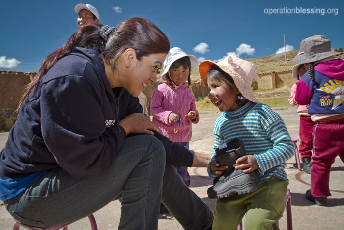 OBI's director of operations for Peru, Dr. Sandra Arbaiza, helps Vivian with her new shoes.,