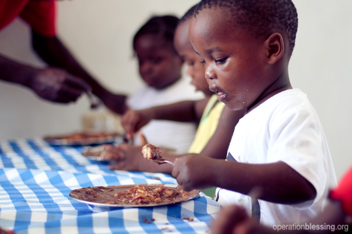 Children at Zanmi Beni Children's Home enjoy fresh tilapia