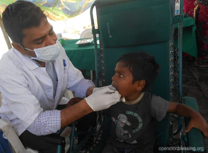 A dentist examines Michael during a mobil clinc visit to his community