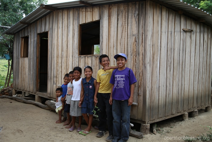 Mirella and her siblings stand in front of their new home.
