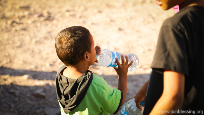 Disaster relief teams distribute safe drinking water to children