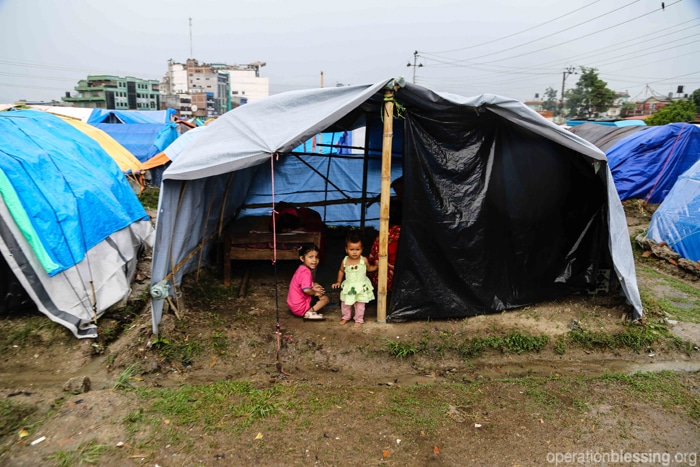 Children huddle under shelter during the monsoon in Nepal