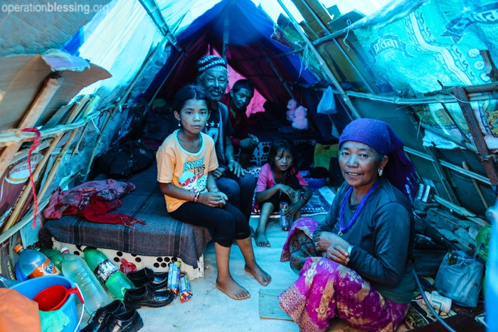 A family keeps dry inside a makeshift tent in Nepal.