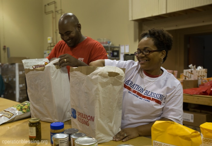 Staff and volunteers pack bags of food for families in need.