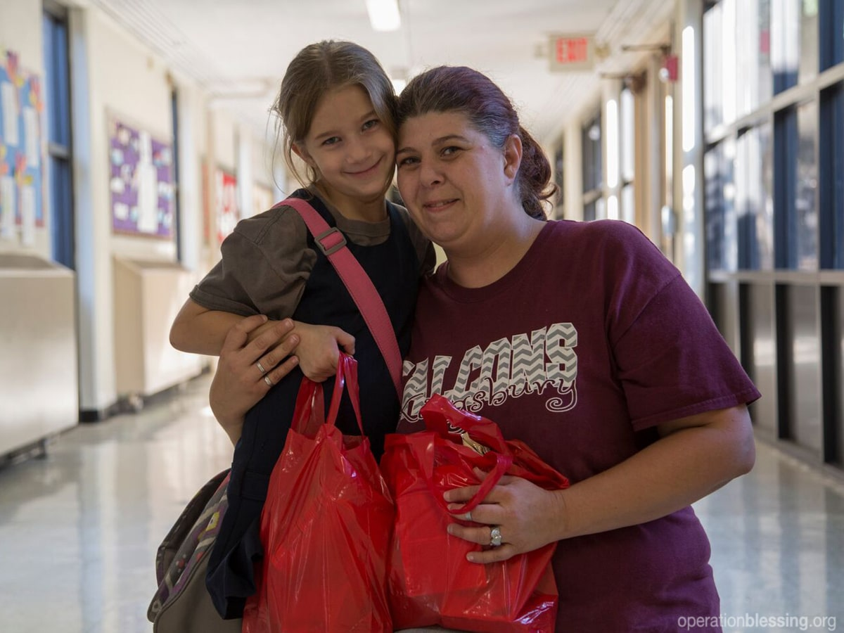 A little girl brings home much-needed groceries each week from Operation Blessing partners