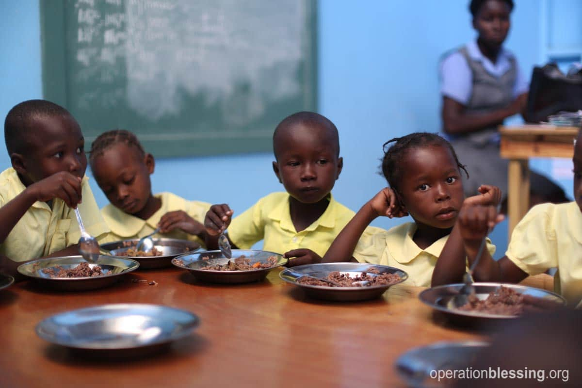 The children at ENLA School in Haiti enjoy a nutritious meal.