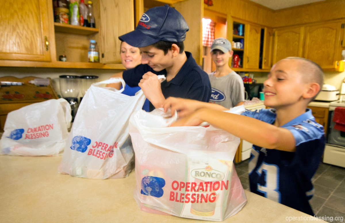 The family puts away food supplies provided by Operation Blessing partners.