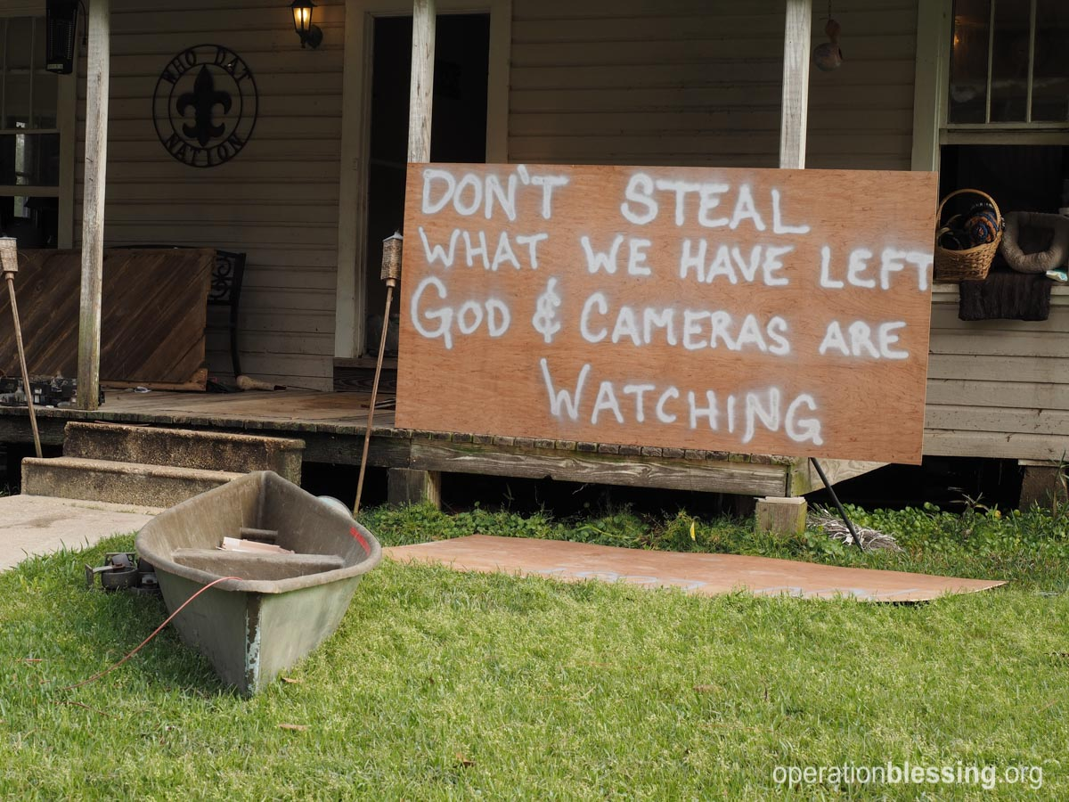 A family places a sign warning off burglars after flood waters in Louisiana devastated their home.