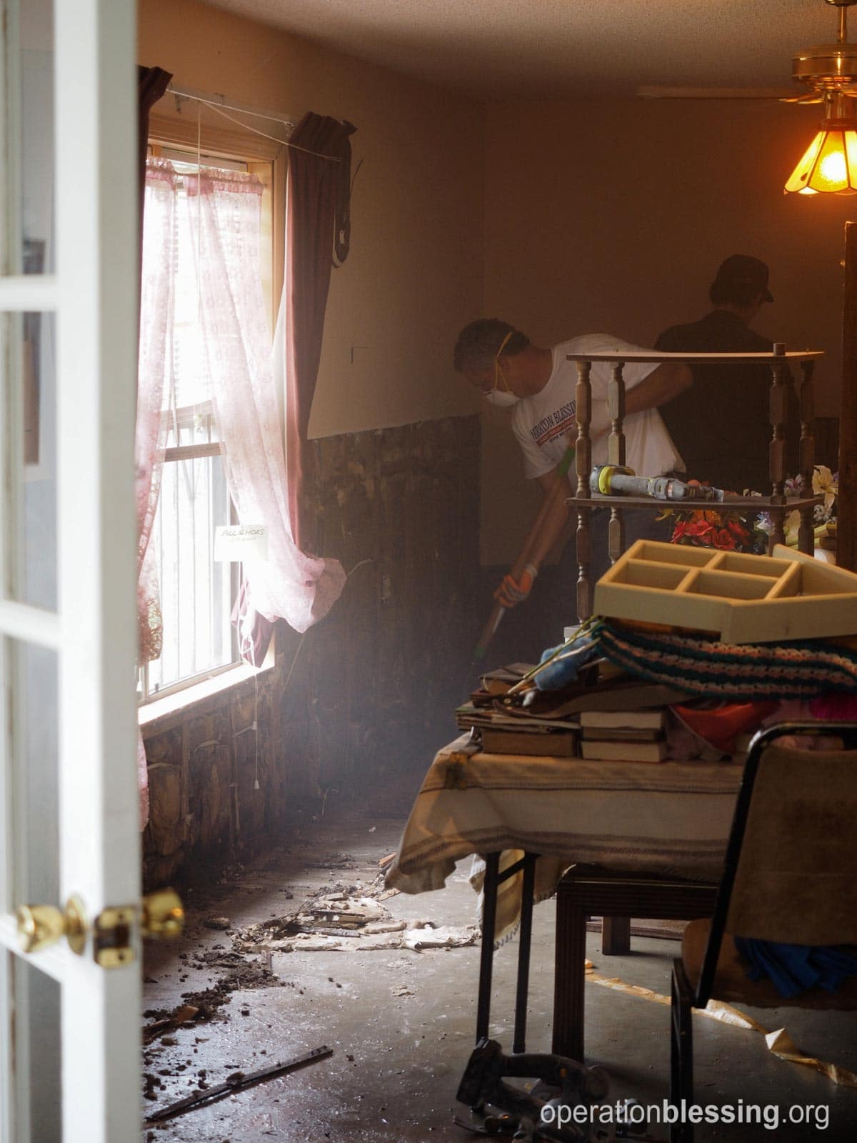 Volunteers work to gut Carol's home and business.