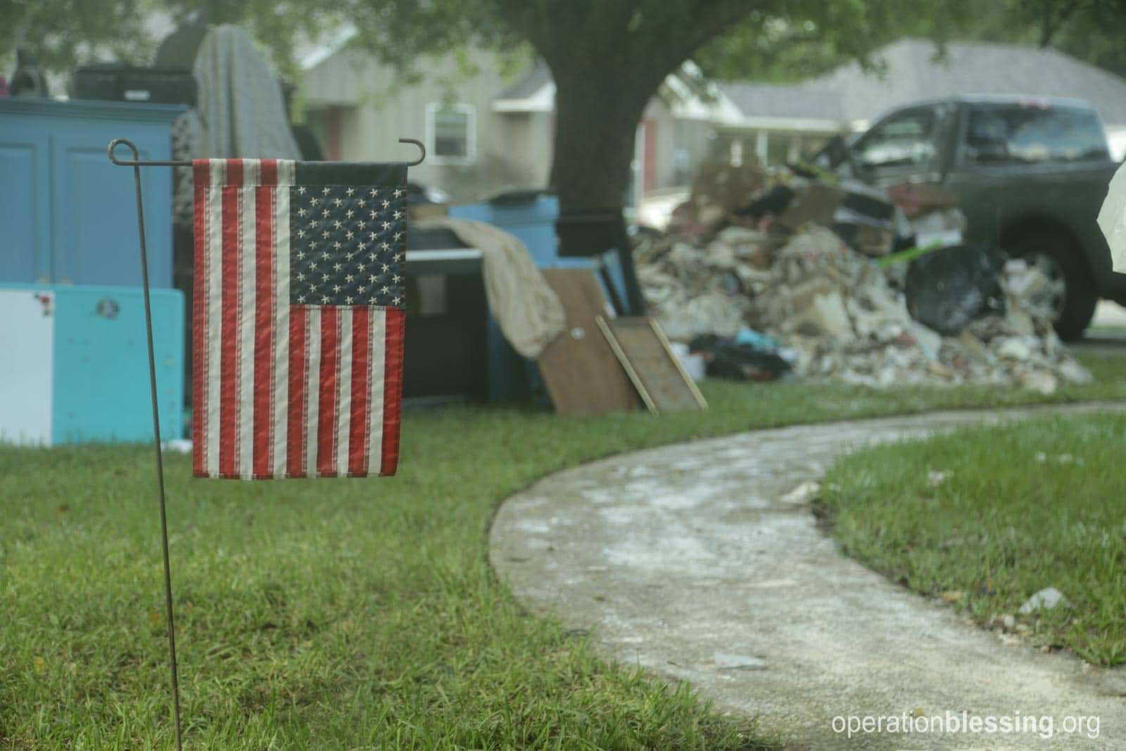 The rubble from the house with an American flag in front.
