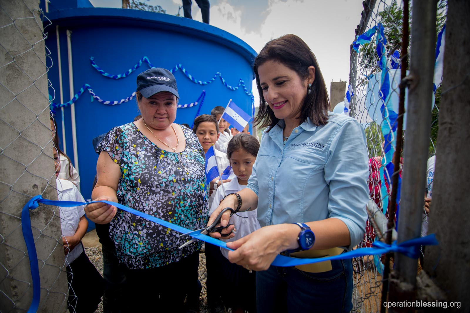 OB Honduras' national director cuts the ribbon on a new safe water project.