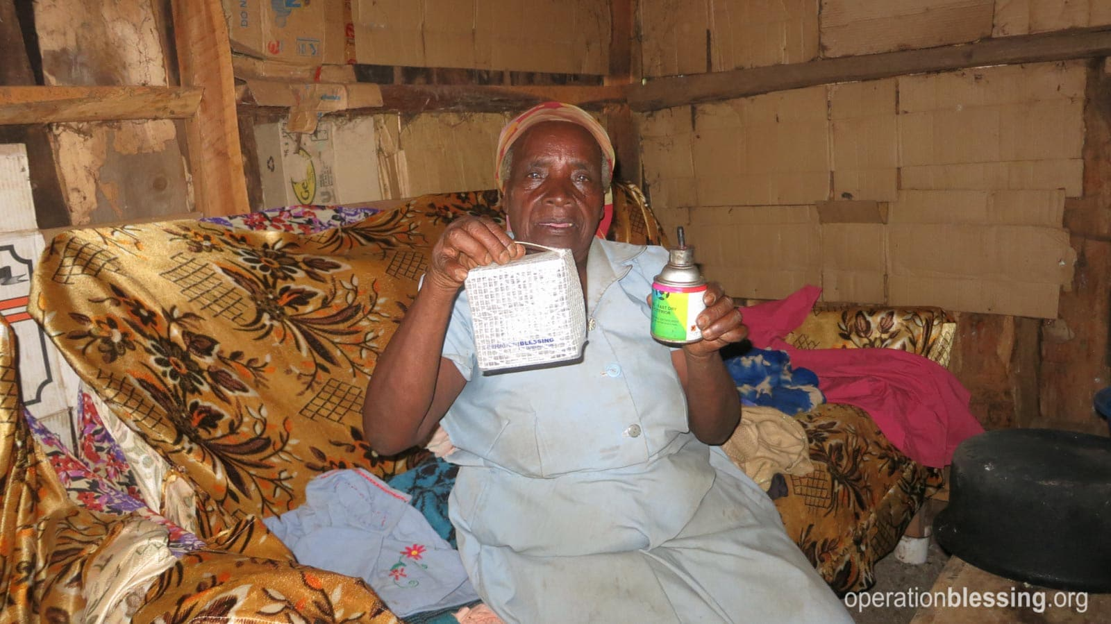 Mary holds up the old kerosene and the new solar light.