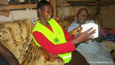 Mary and the Community Health Worker hold a solar light.