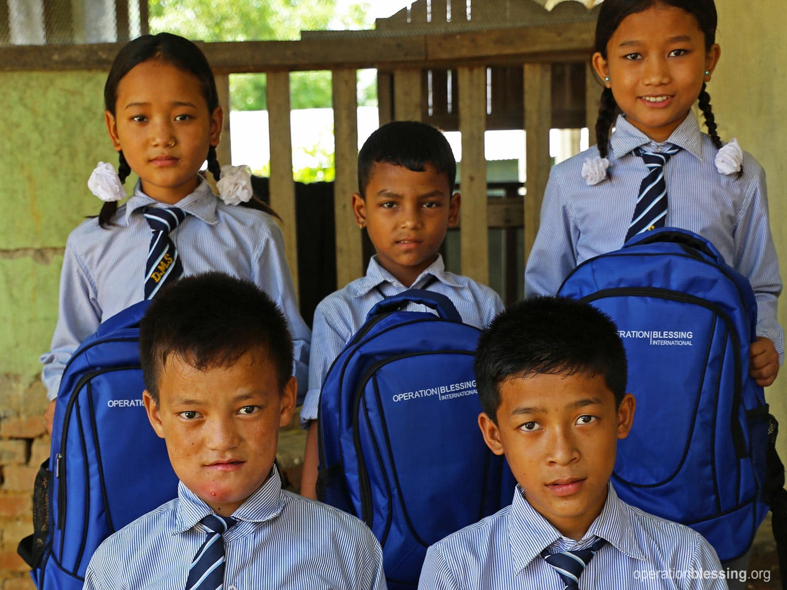 Orphans from the 2015 Nepal earthquake hold their new school supplies.