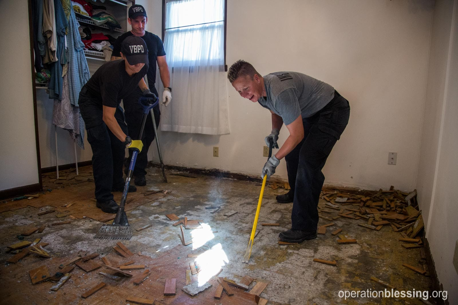 Police recruits serve at Ellen's house tearing up the damaged floor.