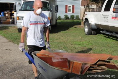 Volunteers remove damaged flooring to provide hurricane help.