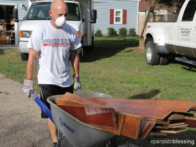 Volunteers remove damaged flooring to provide hurricane help.