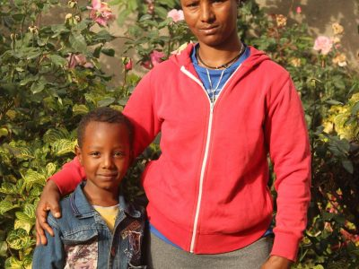 Abebebech, no longer illiterate, stands with her son, Daniel.