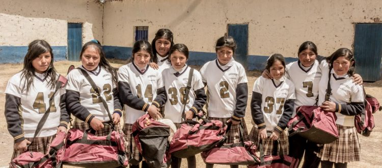 Young women show off their new athletic uniforms and gym bags—all donated by Operation Blessing.