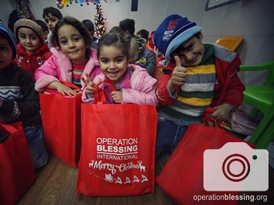 Christian children in Iraq smile with their gift bags.