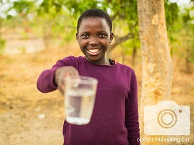 A glass of water from the new water well in Zambia.