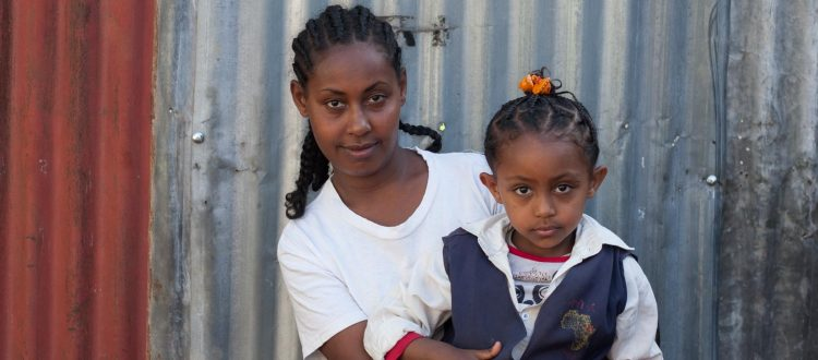 Meseret, a young single mother, holds her daughter, 6-year-old Chen.