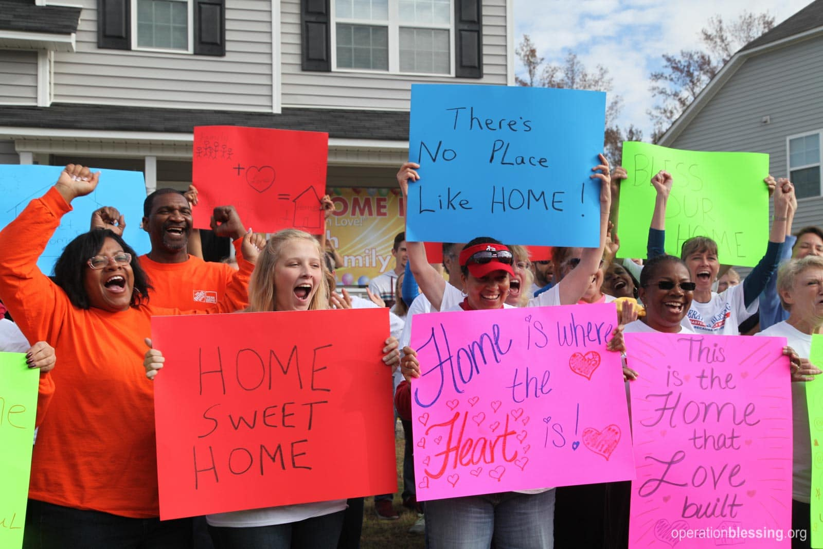 Volunteers welcome the family home.