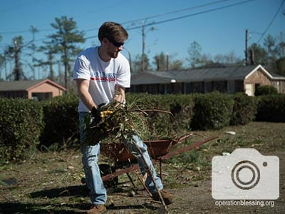 A volunteer rakes to help tornado victims.