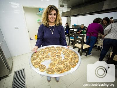 A member of the West Bank church holds up a platter of food.