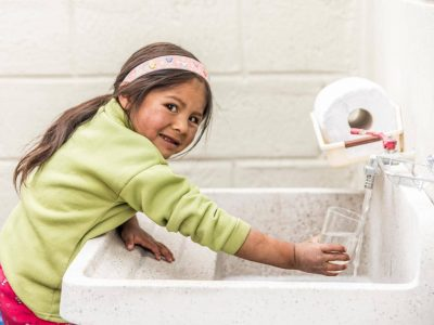 Andrea drinks from the safe water at her school