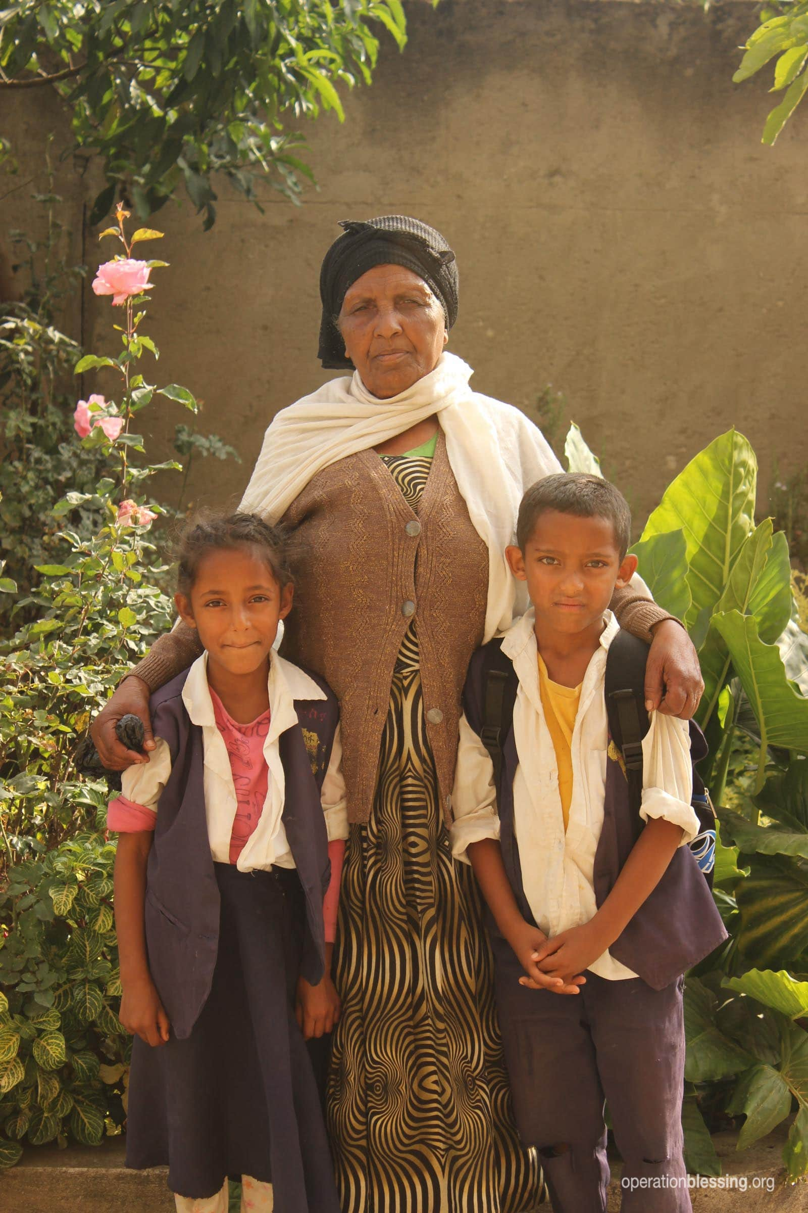 Hibre stands proudly with her two grandchildren.