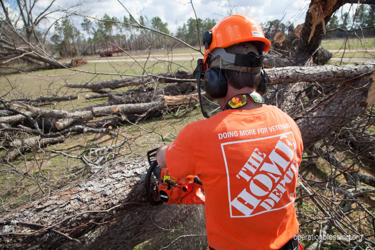 A Home Depot associate works with a chainsaw cutting up trees.