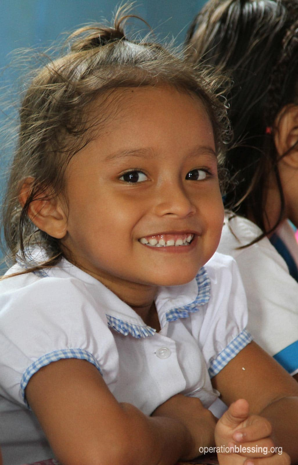 A little girl smiles while enjoying an Operation Blessing provided meal at the San Jose School in Belén.