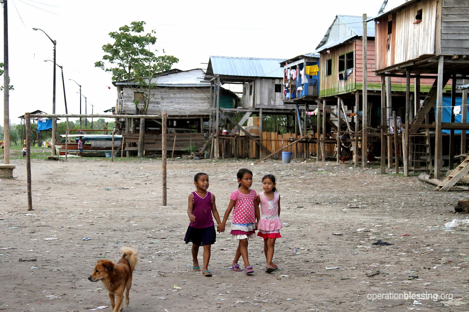 Young girls walk on the muddy streets of Belén during the dry season.