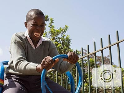 A young boy enjoys his new playground equipment in Tanzania.